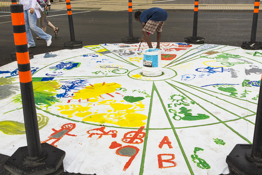 Kids painting on a canvas placed on the ground. Photo Lily Huynh