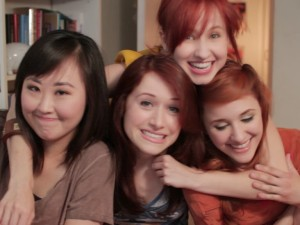 "Screenshot from the web series, ""The Lizzie Bennet Diaries"". Left to right: Julia Cho (Charlotte), Ashley Clements (Lizzie), Mary Kate Wiles (Lydia), and Laura Spencer (Jane). Photo credit: YouTube."